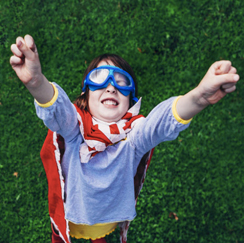 Kid superhero, arms raised, goggles