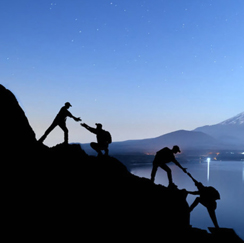 Four people climbing rocks at dusk