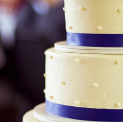White wedding cake with navy blue ribbon