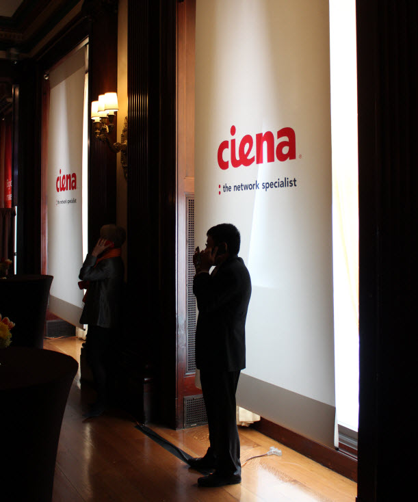 Men the dark on their phones in front of a Ciena banner