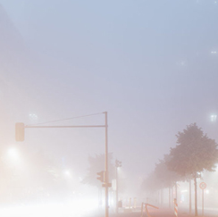 Foggy street with lit street lamps
