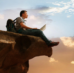 Man sitting with laptop on cliff ledge