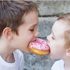 Two kids biting a donut