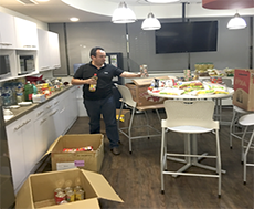 Ciena volunteer standing in breakroom with cartons of food