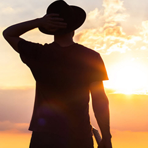 Silhouetted man with hat and sun
